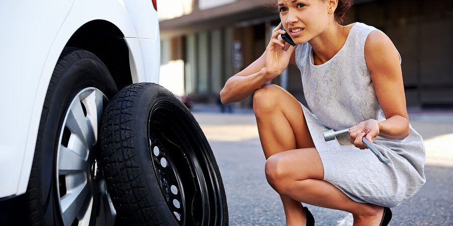 woman calling while fixing the car tire